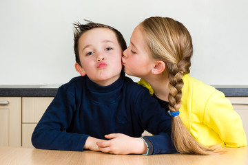 Pretty young girl gives little brother a kiss at home in the kitchen