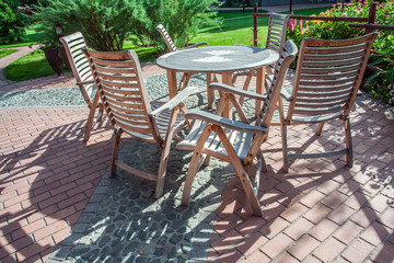 Chairs and glass table on brick terrace at countryside