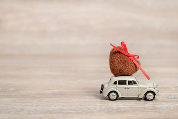 Miniature Car carrying a Heart on roof. Holiday  love concept with copy space. Valentine's day background