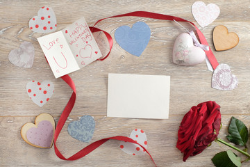 Valentine's day concept with crafted hearts, hand write love message and red rose on wooden background with copy space. Top view