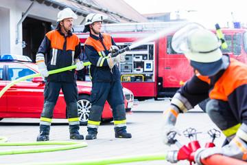 Feuerwehrmänner löschen einen Brand mit Wasserschlauch