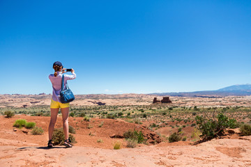 Young woman take pictures at monument valley