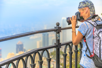 Young travel photographer with professional camera photographing the Victoria Harbour from Victoria Peak, the highest mountain in Hong Kong. Blurred background skyline. Travel and tourism concept.