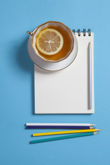 Square notepad on springs with white kraft paper, pencil, cup of tea are on a blue background. Copyspace