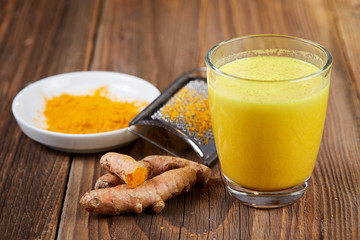 Turmeric curcuma drink with roots on table