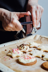 Hands of person adds chocolate as a cookies topping. Vertical studio shot.