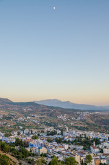 Beautiful historical town Chefchaouen with its blue washed buildings viewed from a hill during sunset, Morocco