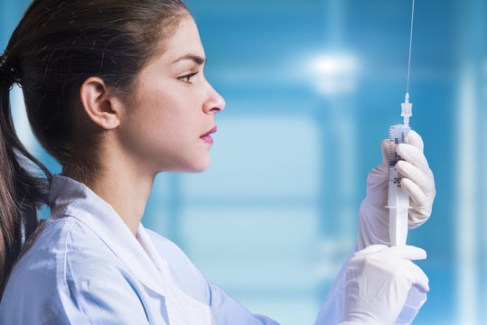 concept of a woman doctor that is preparing an amniocentesis needle for amniotic fuid extraction