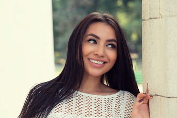 Closeup portrait of confident smiling happy pretty young woman in white shirt