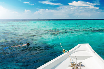 Wall Mural - White yacht at clear ocean near coral reef, woman snorkeling