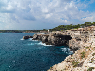 Mallorca cliff with cave and cloudy sky