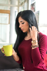 Pretty young woman sitting in the cafe with a cup of tea.