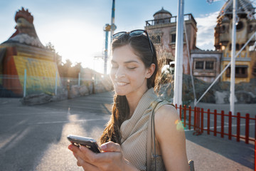 woman is using an app in her smartphone device to send a text message in front of an amusement park