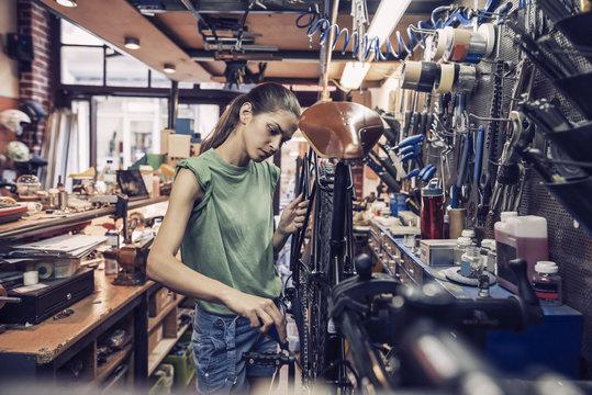 woman bicycle engineer is repairing a bike in the workshop