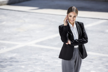 Beautiful young business woman is talking on the phone while looking down. With copy space.