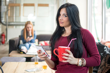 Smiling young woman with coffee cup and smartphone at cafe. Girl using smartphone in the background.
