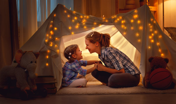 happy mother and daughter playing at home in tent .