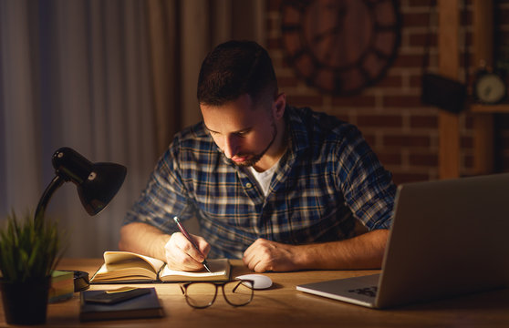 man working on computer at home at night in dark .