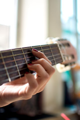 Young female play on the acoustic guitar.
