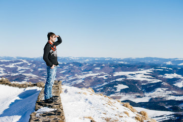 A tourist is looking for the right way in winter mountains