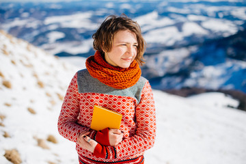 Woman in warm sweater is reading a book during the travel in win
