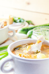 Cheese soup with chicken, herbs and vegetable. Cheese, cucumbers and herbs on wooden table. Light background