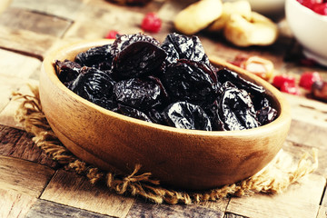 Dried sweet prunes or dark plums in bowl on wooden background, s