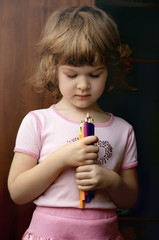 Portrait of the beautiful kid girl with colorful pencil.