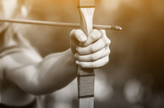 Athlete aiming at a target and shoots an arrow. Archery.