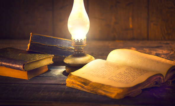 Old oil lamp and old books in darkness. Vintage kerosene lantern and open old book with blank pages on wooden table