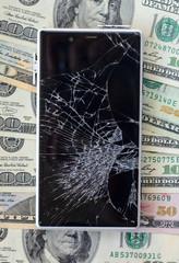 Smartphone with broken displayon money background. Loss of money concept