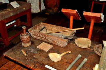 Guilford, Connecticut - July 10, 2015:  17th century colonial kitchen utensils are displayed on a kitchen table at the 1639 Henry Whitfield House and Museum