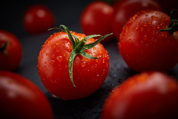 Fresh cherry tomatoes on black background