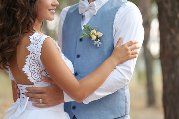 Wedding couple outdoors on blurred background, close up view