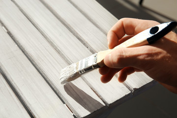 Close up view of human hand painting furniture