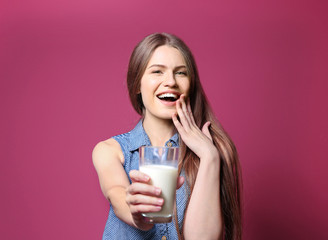Beautiful young woman with glass of milk on color background