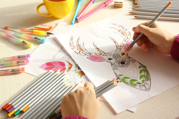 Woman sitting at table with coloring pictures for adults, closeup