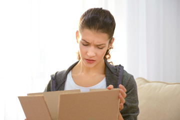Beautiful young woman opening box with parcel at home