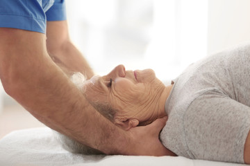Physiotherapist working with elderly patient in clinic, closeup