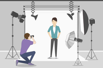 Male model in photo studio. White background with lights and cameras. Photographer making photos. Fashion clothes.