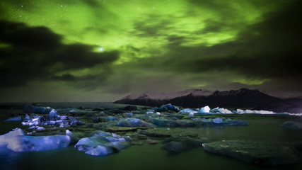 Panoramic view of iceberg and northern lights