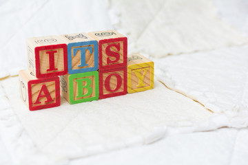 Wooden Alphabet Blocks on Quilt Spelling Its A Boy Angled