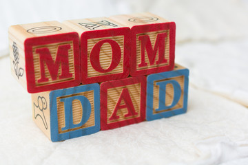 Wooden Alphabet Blocks on Quilt Spelling Mom and Dad
