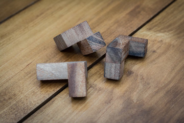 Wooden Block Brain Teaser on Wood Background Pieces Close Up
