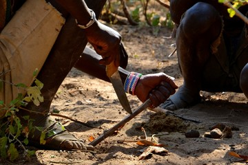 Hadzabe men carving wood to assist in lighting a fire.