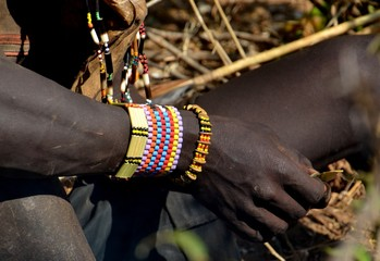 Bracelets standing out against the dark skin of a Hadzabe man in Tanzania.