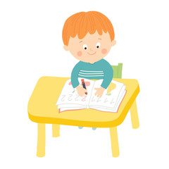 Cute school boy writing at desk in classroom