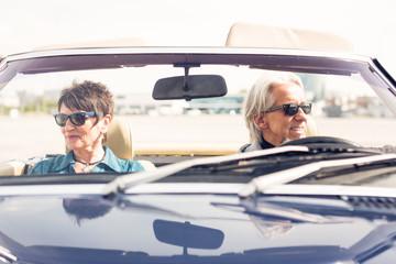 Senior Couple Driving A Convertible Classic Car