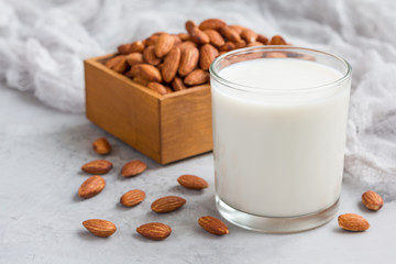 Almond milk in glass with almonds on background, horizontal, copy space