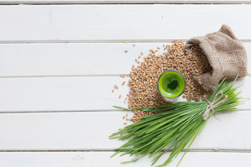 Green organic wheat grass drink over white wood background,top v